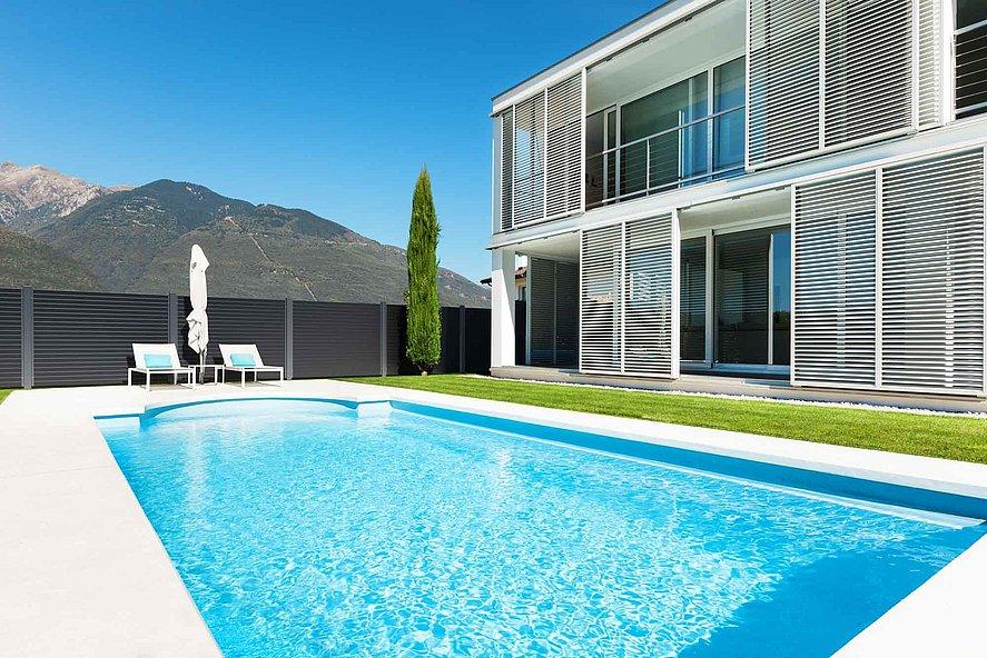 Villa architecturale avec piscine entourée par une clôture occultante moderne en aluminium - vue sur les montagnes