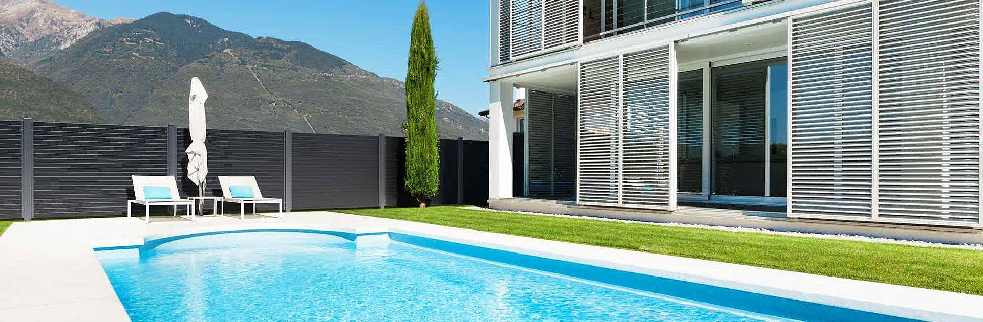 Villa architecturale avec piscine entourée par une clôture moderne en aluminium - vue sur les montagnes