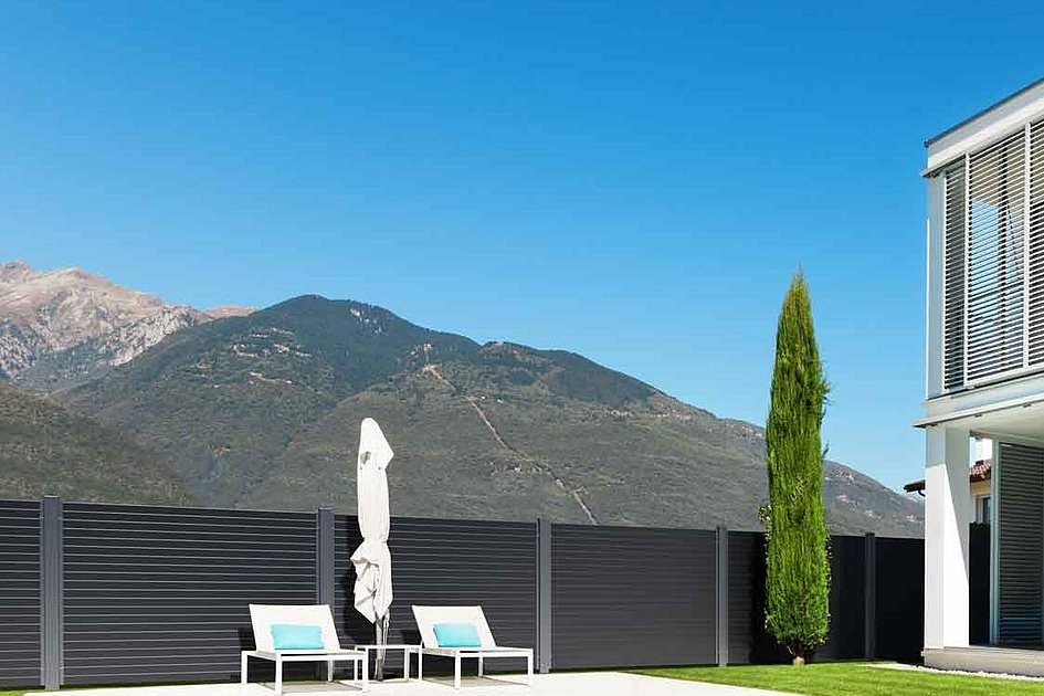 maison moderne avec piscine dans le jardin et vue sur les montagnes, entourée d'une clôture en aluminium