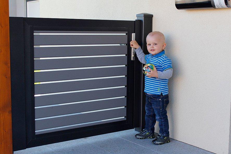 Un petit enfant se tenant devant le portillon de jardin occultant au design moderne