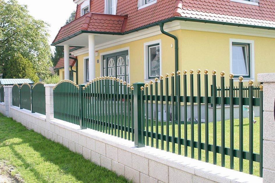 [Translate to Fransösich:] Palisadenzaun aus Aluminium in grün mit goldigen Abschlusskappen vor einem Einfamilienhaus