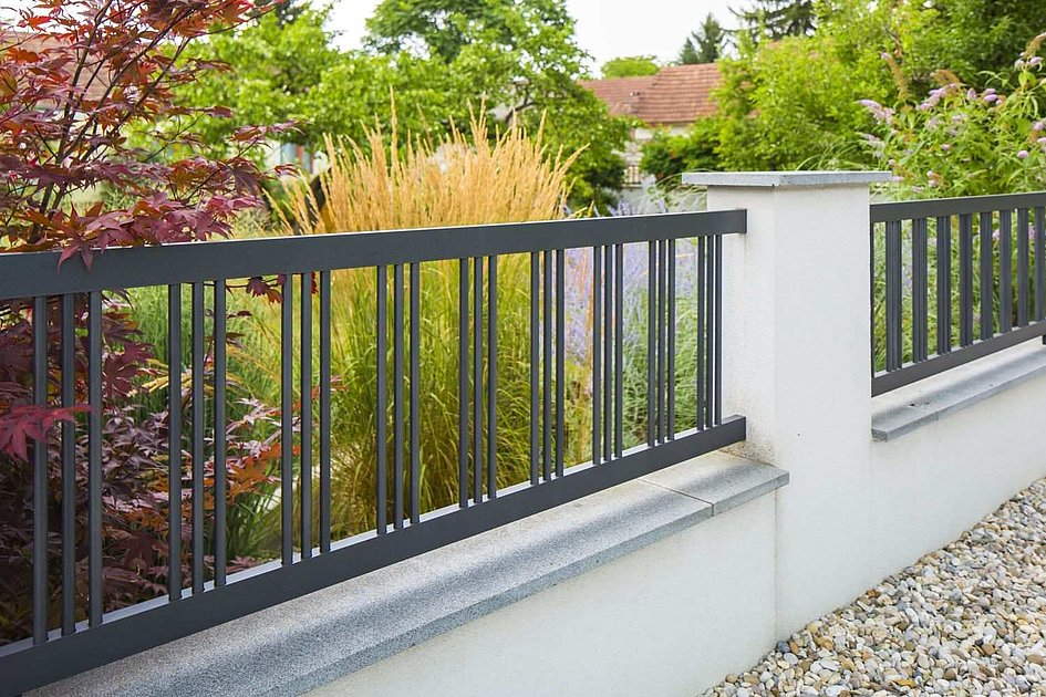 Clôture de jardin en aluminium couleur grise sur mur et colonnes bétonnées