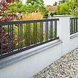 Clôture à barres couleur anthracite avec barres simples sur socle blanc avec un lit de gravier et des plantes