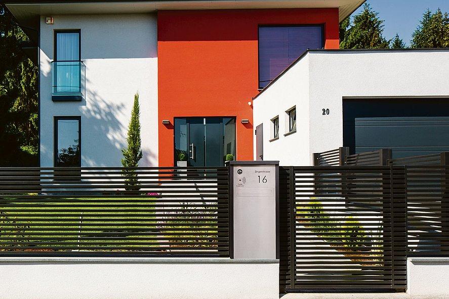 Colonne-boîte aux lettres couleur argent intégrés à une clôture à lattes moderne MAGNUS couleur anthracite, devant une maison cubique moderne