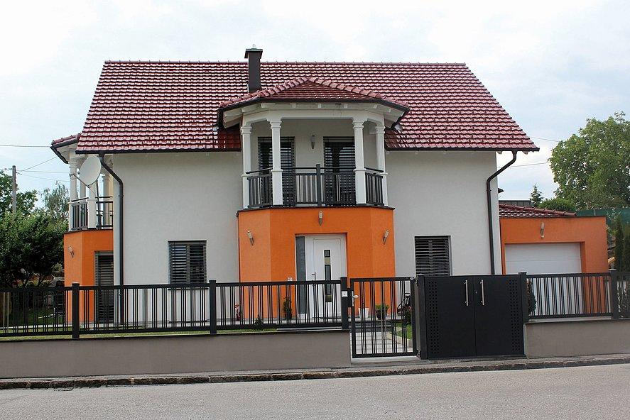 Clôture à barres avec portail de jardin couleur anthracite et portail central de la grande maison unifamiliale avec entrée moderne et balcon à colonnes