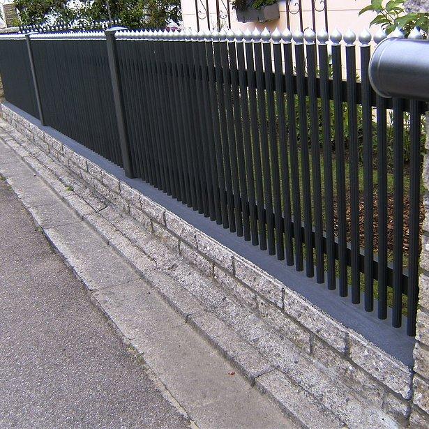 Clôture à palissade couleur anthracite avec caches coupe oignon couleur argent sur socle en pierre maçonné