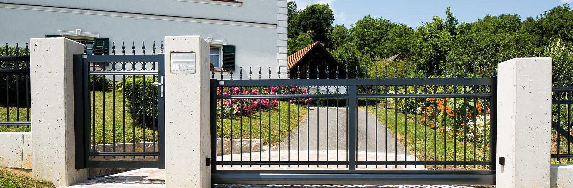 Portail coulissant et portillon de jardin en aluminium finition ferronnerie d'art devant un grand jardin