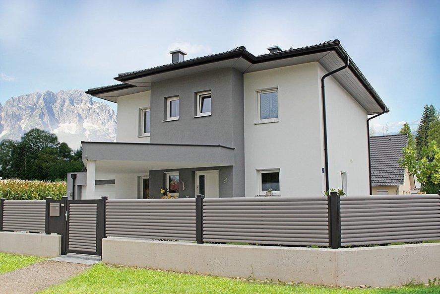 Clôture et portillon de jardin à lamelles grises avec poteaux et cadre gris foncé devant une maison blanche et grise