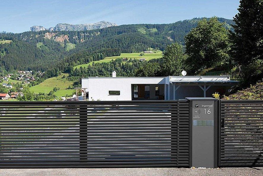 Portail à double battant avec lamelles modernes couleur anthracite et portillon de jardin pour une maison à architecture moderne dans les montagnes