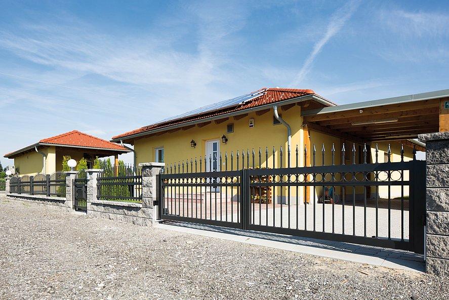 portail à double battant élégant avec clôture à barres et portillon de jardin couleur anthracite avec ornements devant un grand domaine avec maison méditerranéenne