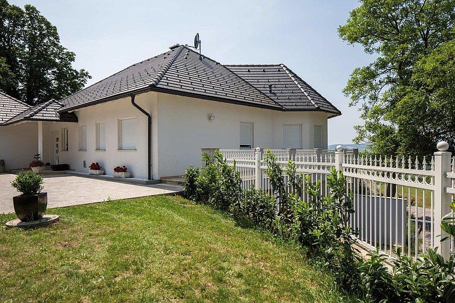 Clôture à barres couleur blanche finition ferronnerie d'art, clôture à barres entourant un bungalow avec jardin