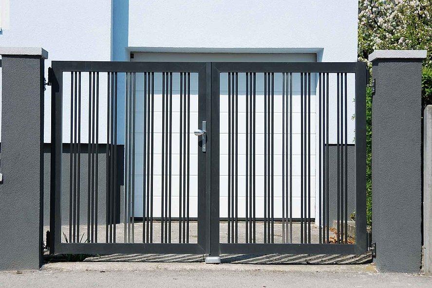 Portail à double battant couleur anthracite entre des colonnes murales grises devant une entrée de garage