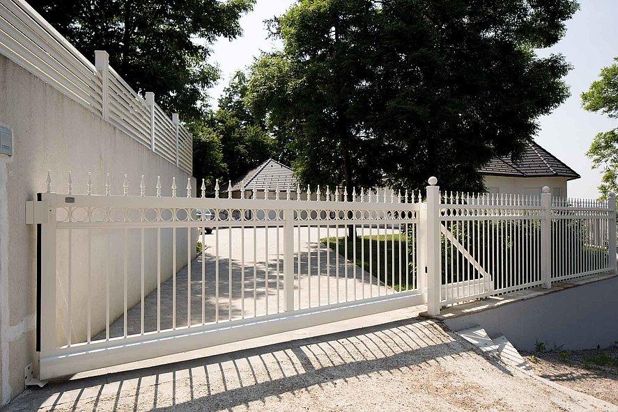 Portail coulissant sur clôture à barres blanche, clôture à barres finition ferronnerie d'art devant une grande entrée
