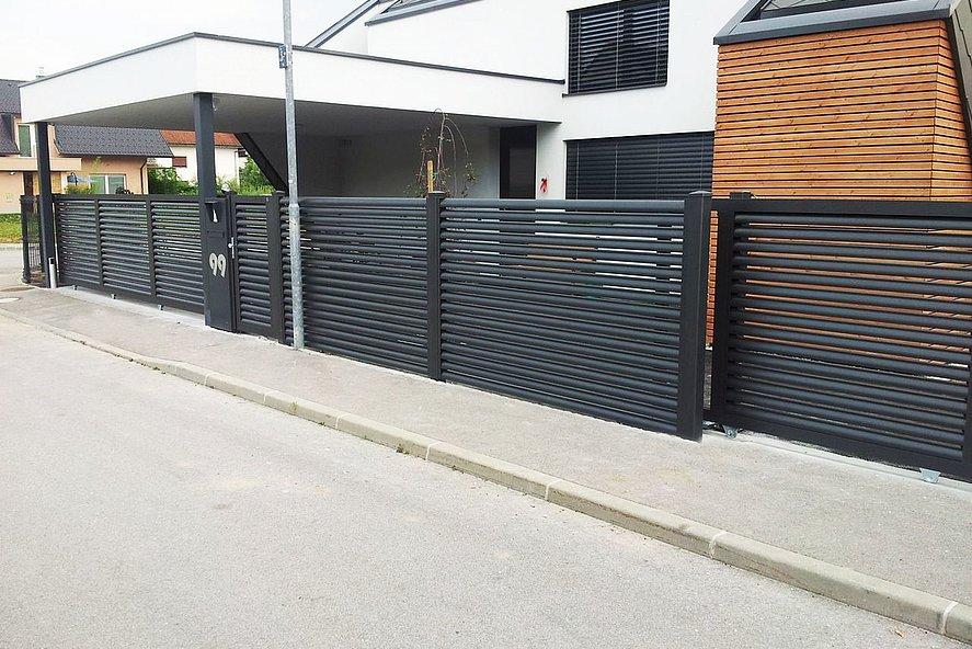 Clôture à lamelles occultante en aluminium couleur anthracite devant une maison unifamiliale moderne en France