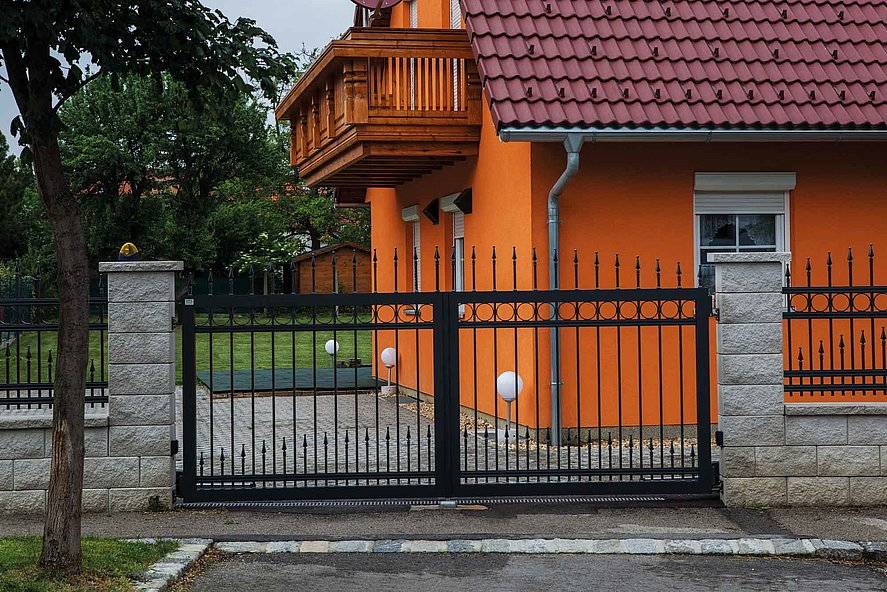 Portail à double battant avec barres noires en aluminium sur clôture à barres autour d'une maison orange