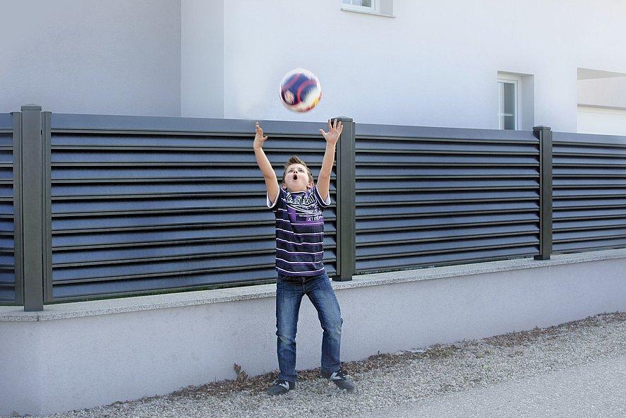 Enfant lançant une balle devant la clôture de jardin à lamelles couleur anthracite sur socle mural blanc