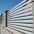 Vue rapprochée d'une clôture de jardin à lamelles couleur gris aluminium sur socles muraux, avec une jeune fille qui ouvre le portillon