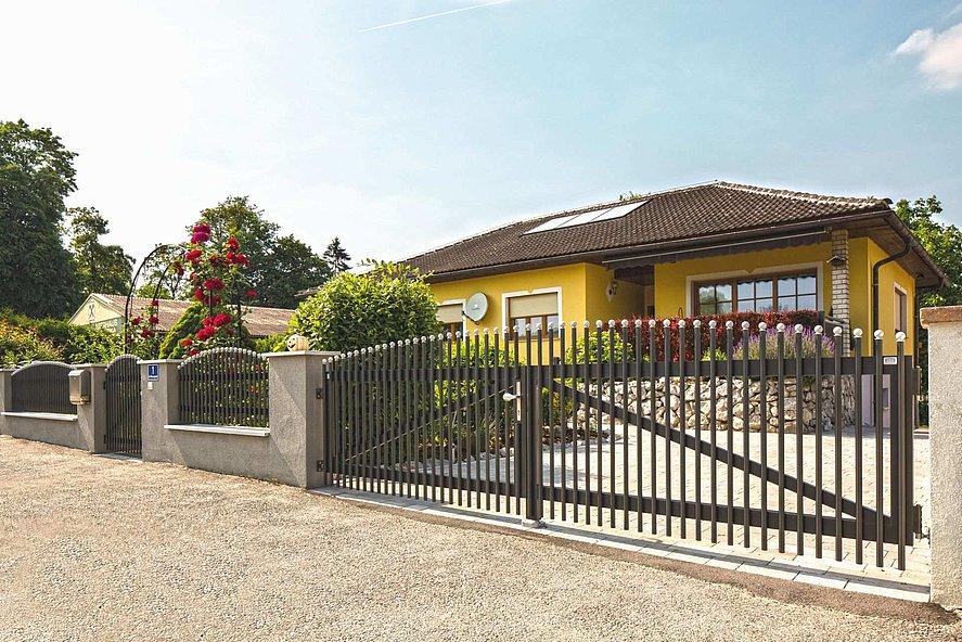 Portail à double battant avec palissades couleur gris clair et embouts coupe oignon blancs servant de porte d'entrée à un grand bungalow