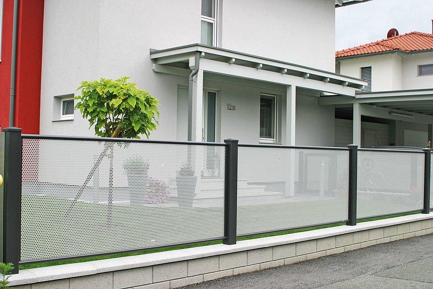 Vue rapprochée d'une clôture de jardin en tôle perforée en gris et anthracite dans un quartier résidentiel
