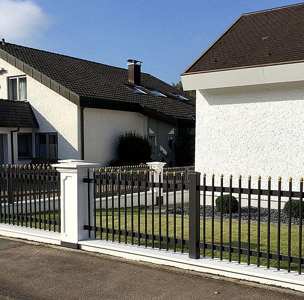 Clôture à palissade couleur noir-or entre des socles muraux classiques dans un domaine de maison unifamiliale