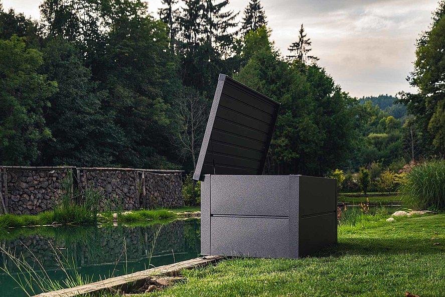 Coffre de rangement couleur anthracite dans un jardin avec bassin naturel et conifères
