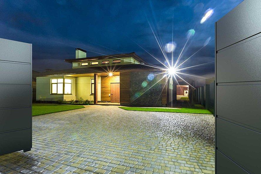 portail à double battant occultant ouvert permettant de voir l'entrée d'une villa moderne dans la nuit