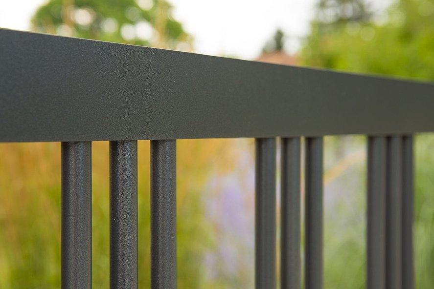 Plan rapproché d'une clôture de jardin avec triple rangée de barres simples en aluminium