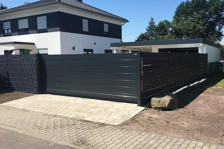 portail coulissant occultant moderne sur clôture occultante couleur anthracite entourant une grande maison unifamiliale