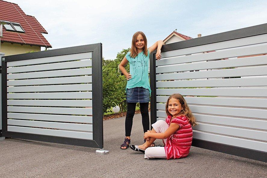 Des jeunes se tenant sur le portail à double battant à lattes en aluminium modernes couleurs grise et anthracite