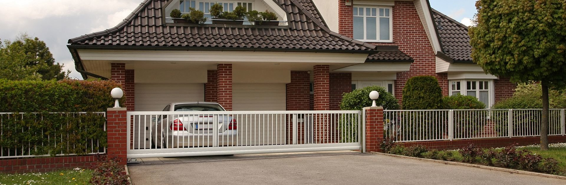 [Translate to Fransösich:] Staketenzaun aus Aluminium in weiß mit Gartentor als Umzäunung für ein Einfamilienhaus im klassischen Stil