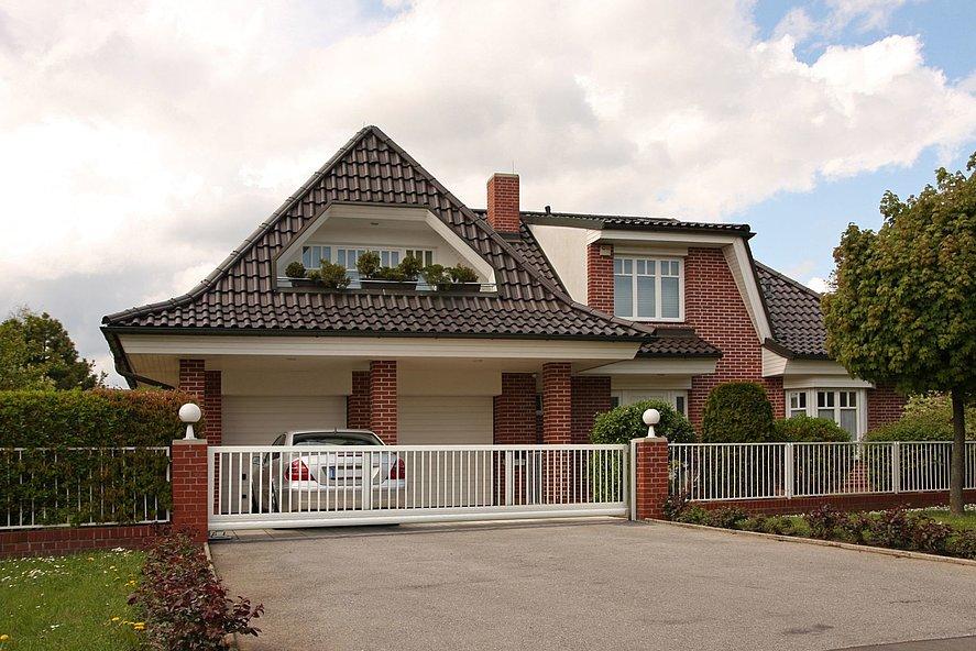 Portail coulissant blanc avec clôture à barres devant une maison de maître avec façade en brique