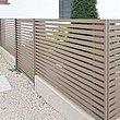 clôture de jardin clair et moderne avec portillon de jardin couleur sable fin sur un socle discret