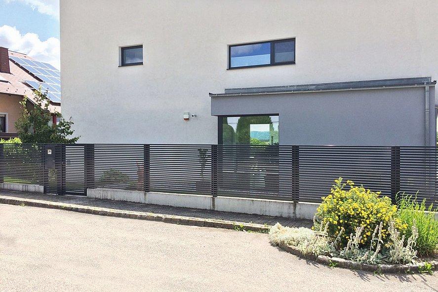 clôture de jardin moderne avec lattes transversales couleur anthracite devant une maison cubique moderne