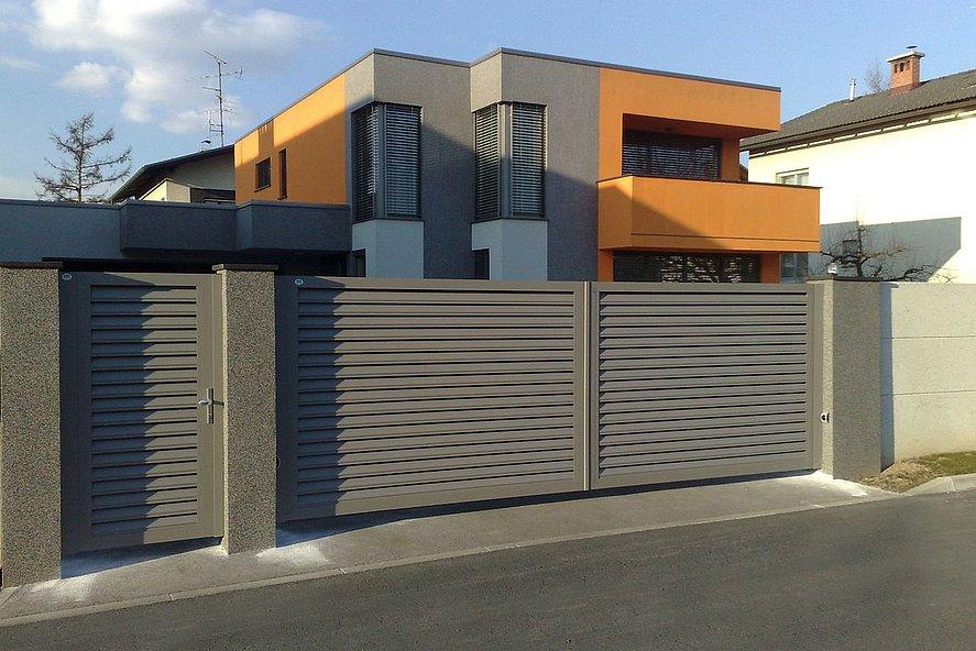 Portillon de jardin et portail coulissant à lamelles grises devant une maison à architecture moderne orange et grise