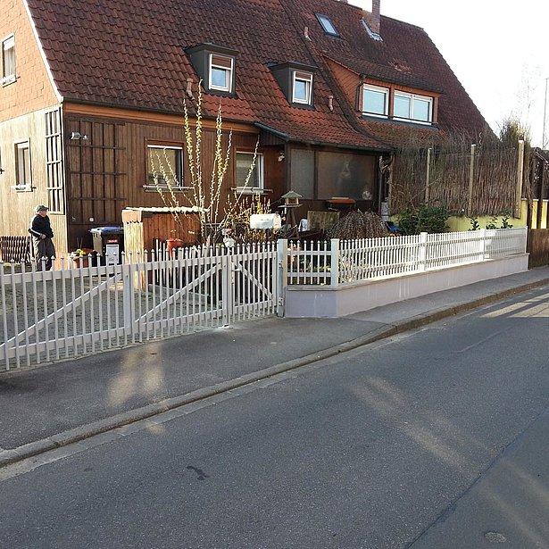 clôture à palissade blanche avec portail d'entrée avant la rénovation de la clôture