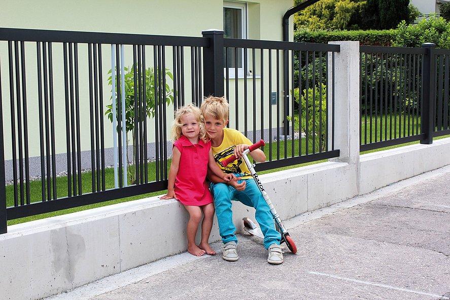 Clôture de jardin en aluminium avec une triple rangée de barres couleur anthracite sur un socle mural blanc, devant laquelle se tiennent deux enfants joue à joue avec une trottinette
