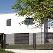 Clôture de jardin entièrement moderne avec lattes transversales claires couleur anthracite devant une maison cubique