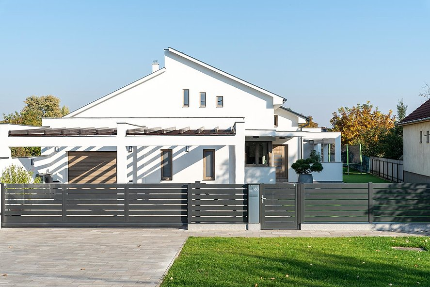 Portail coulissant, clôture et porte piétonne à lattes transversales larges et colonne-boîte aux lettres intégrée couleur anthracite sur socles en briques devant une maison architecturale moderne