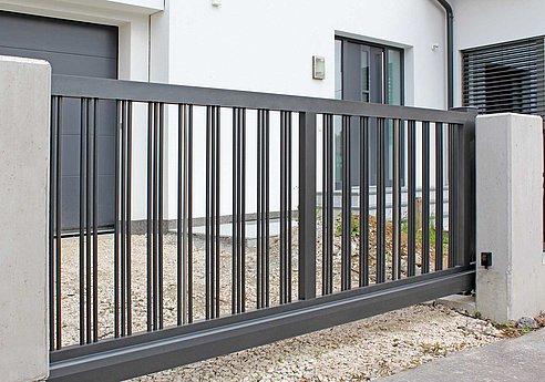 Portail coulissant couleur anthracite avec triple rangée de barres devant une entrée de garage