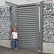 Portillon de jardin à lamelles grises comme entrée de la clôture en gabions avec une petite fille dans l'allée