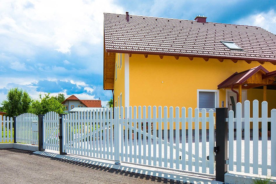 Portail à double battant avec clôture à lattes classique blanche devant une maison unifamiliale jaune
