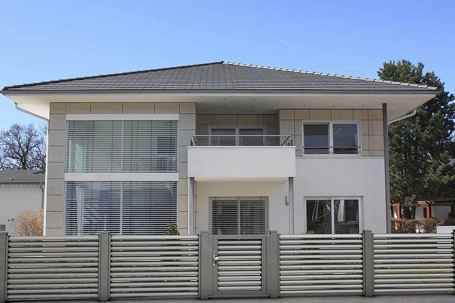 Clôture à lamelles couleur argent avec portillon de jardin devant une maison à deux niveaux en blanc et gris