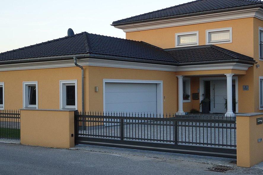 portail coulissant électrique avec clôture à barres finition ferronnerie d'art à l'entrée d'une maison au style méditerranéen
