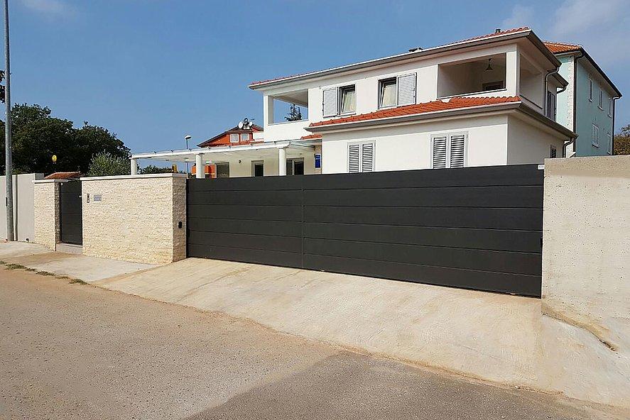 portail coulissant électrique et portillon de jardin occultant sur clôture en briques, servant de protection à une villa moderne en arrière-plan