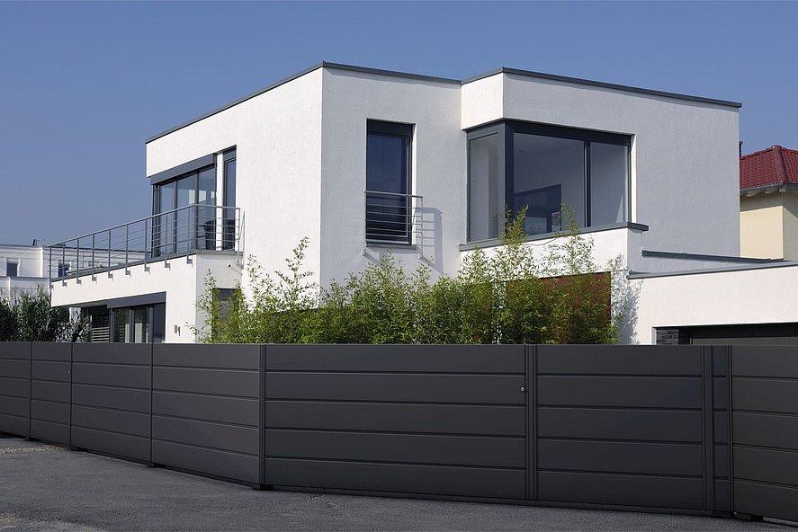 clôture de jardin occultante moderne couleur anthracite devant une maison à architecture moderne avec beaucoup d'herbe