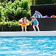 Coffre de rangement couleur anthracite, avec des enfants qui sautent dans la piscine