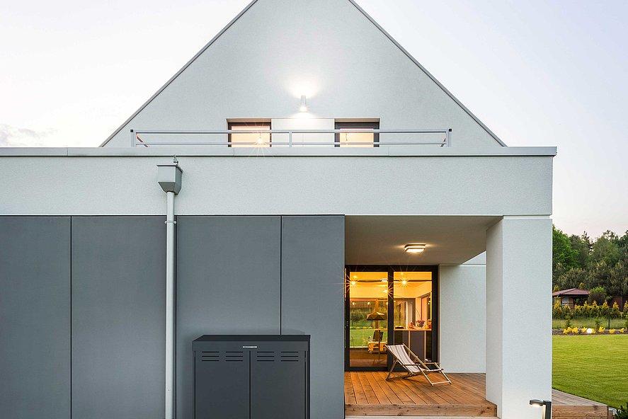coffre multifonctions moderne couleur anthracite devant une maison unifamiliale moderne avec toit pointu et terrasse
