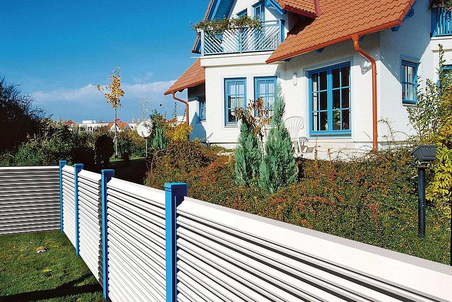 Clôture de jardin avec lamelles blanches et poteaux bleus entourant une maison style années 90 avec cadres de fenêtres bleus