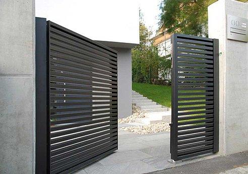 portail de jardin moderne ouvert entre des socles muraux, devant une maison moderne