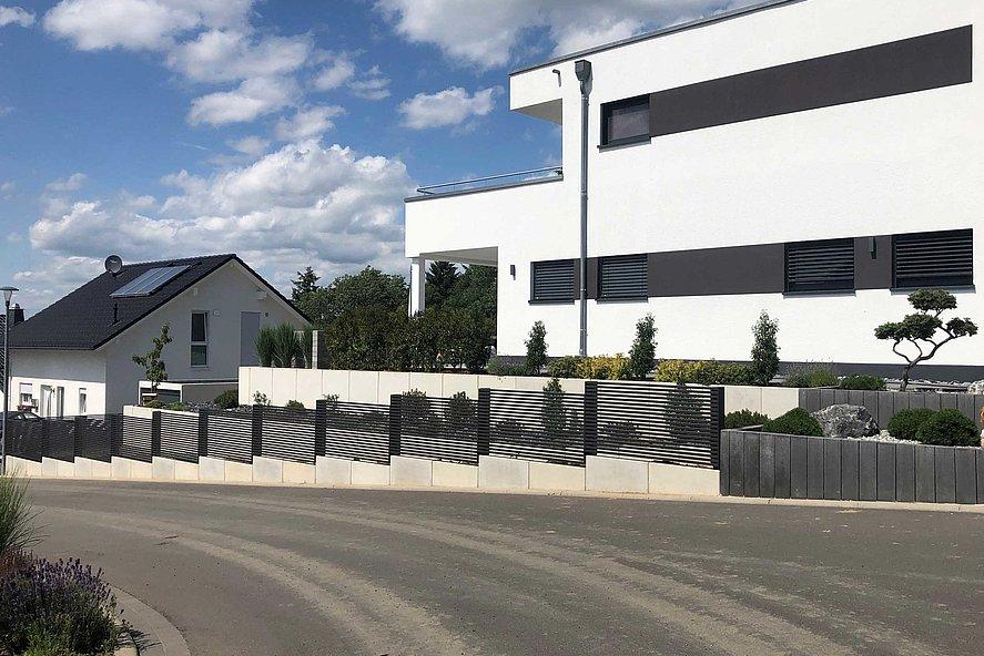 Clôture de jardin modèle MAGNUS couleur anthracite devant un bloc d'habitat moderne blanc